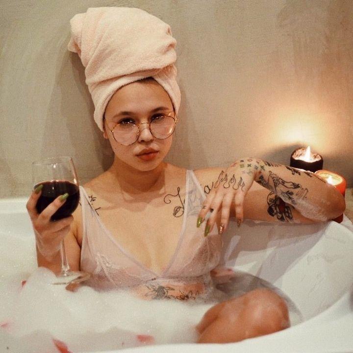 Инстасамка в ванной пьёт вино